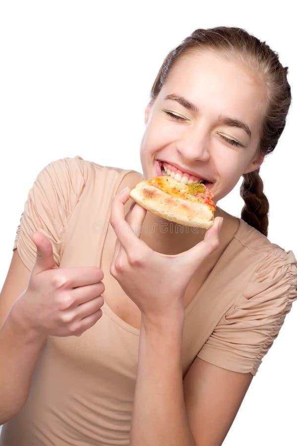 Mooi meisje die pizza eten en duim tonen royalty-vrije stock afbeeldingen