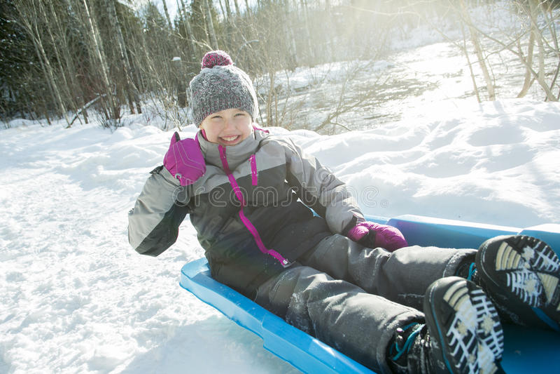 Mooi meisje die pret op oude slee op de winter hebben stock afbeeldingen