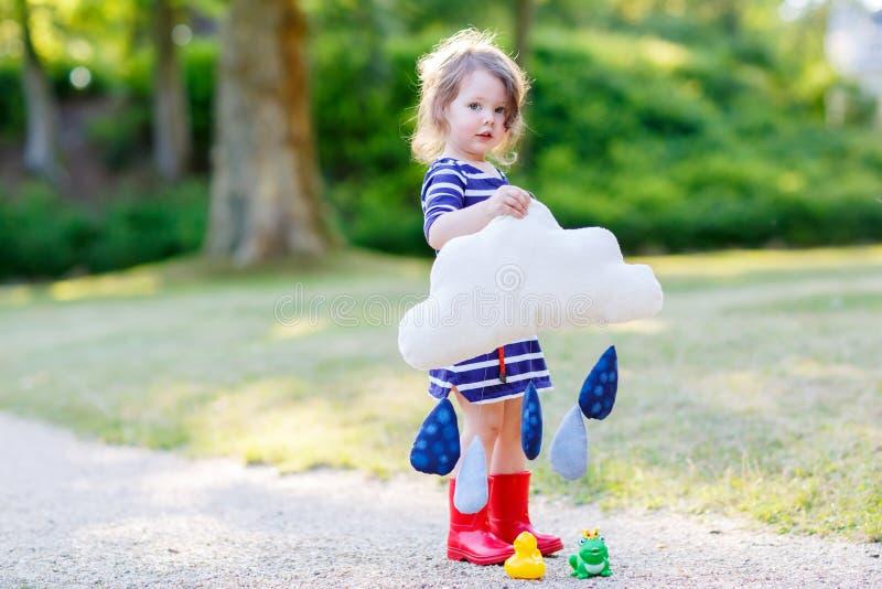 Mooi meisje die in rode regenlaarzen met stuk speelgoed raindro spelen royalty-vrije stock afbeelding