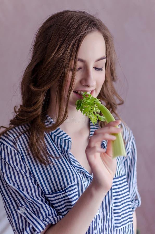 Mooi meisje die selderie eten royalty-vrije stock afbeelding
