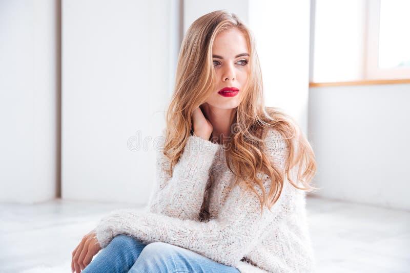 Mooi meisje die sweater en rode lippenstiftzitting thuis dragen stock foto's
