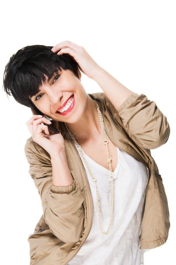 Mooi meisje die terwijl het gebruiken van celtelefoon glimlachen royalty-vrije stock foto's