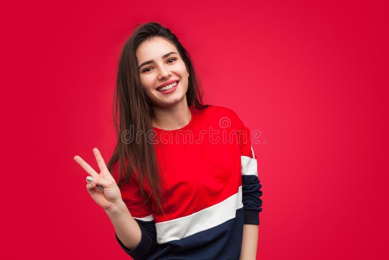 Mooi meisje die twee vingers op rood tonen stock foto