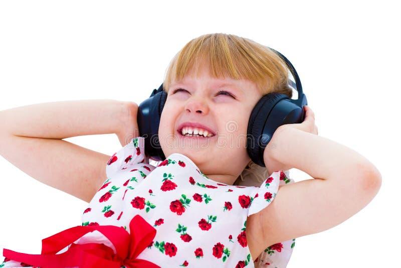 Mooi meisje die in witte kleding aan muziek met hea luisteren royalty-vrije stock afbeeldingen