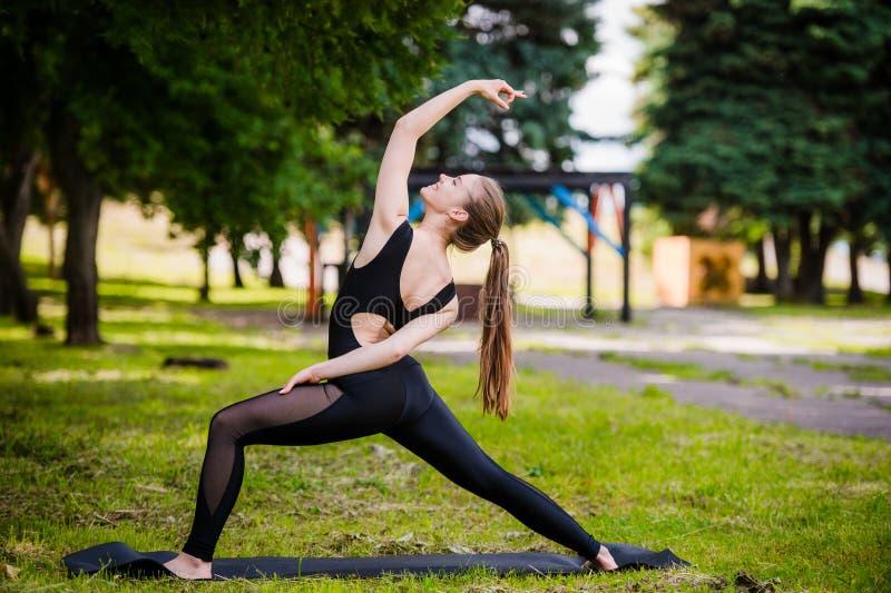 Mooi meisje die yoga op groen gras in park doen bij de zomerochtend stock afbeeldingen