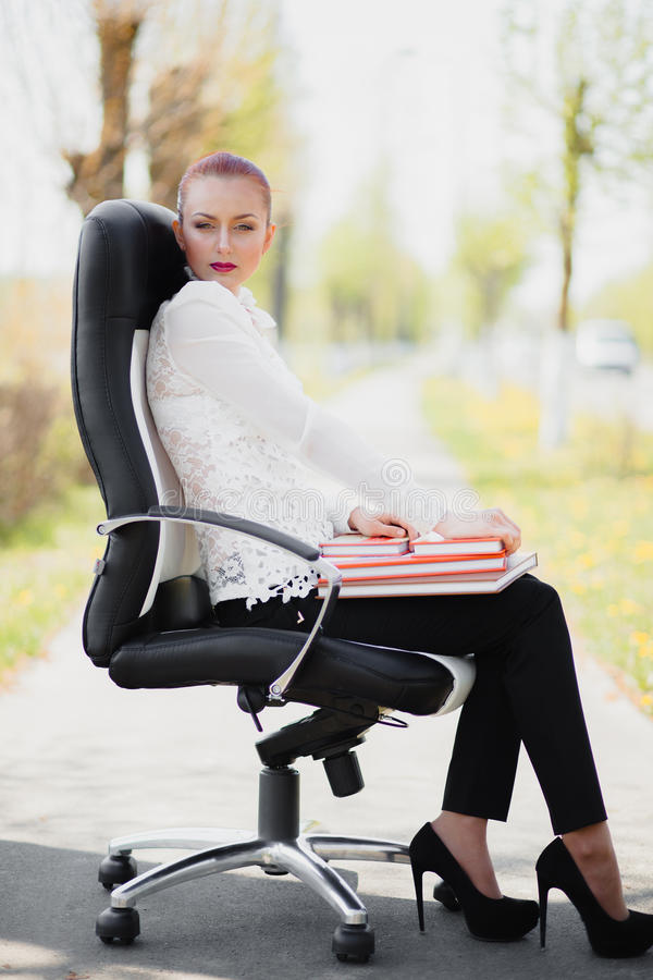 Mooi meisje die zich bij de stoel bevinden stock foto