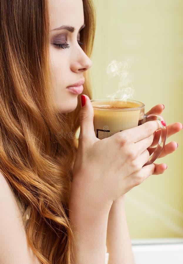 Mooi meisje die zich bij het venster met een hete Kop van vroeg het stimuleren van koffie in de ochtend bevinden royalty-vrije stock foto