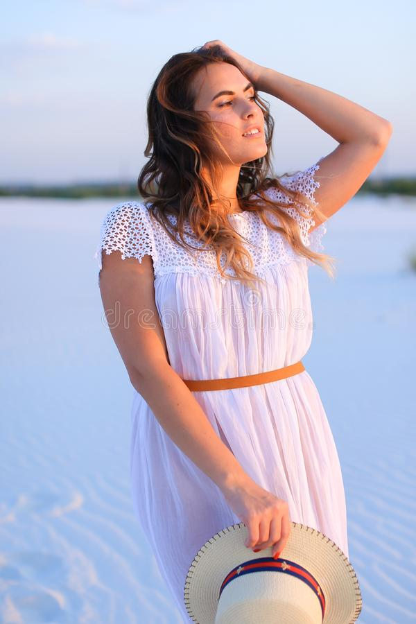 Mooi meisje die zich bij wit zand, het dragen van kleding en het houden bevinden stock fotografie