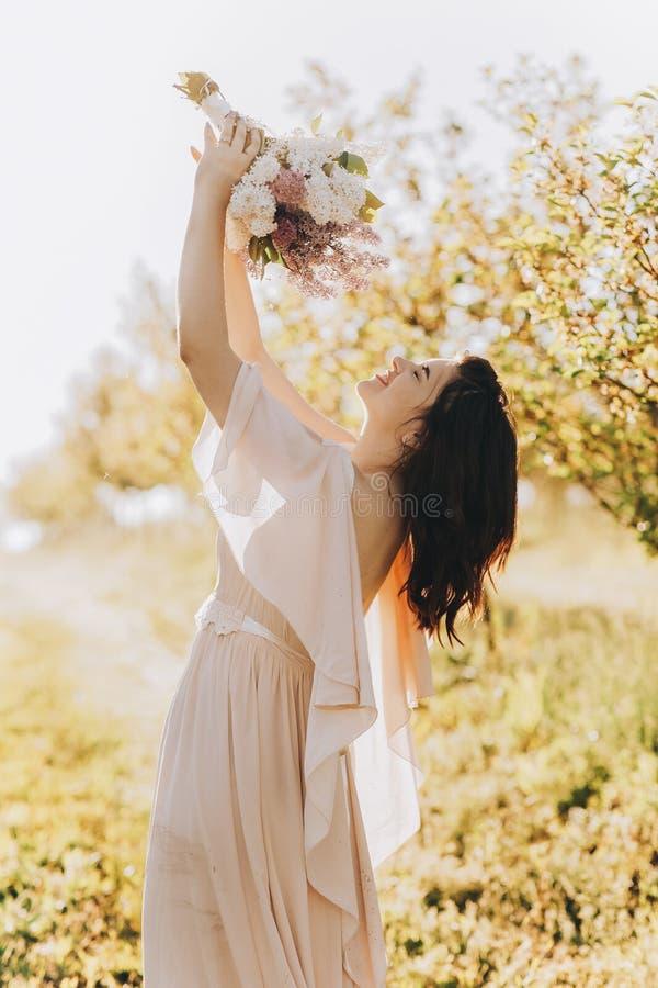 Mooi meisje die zich in een appeltuin bevinden en een boeket snuiven stock foto's