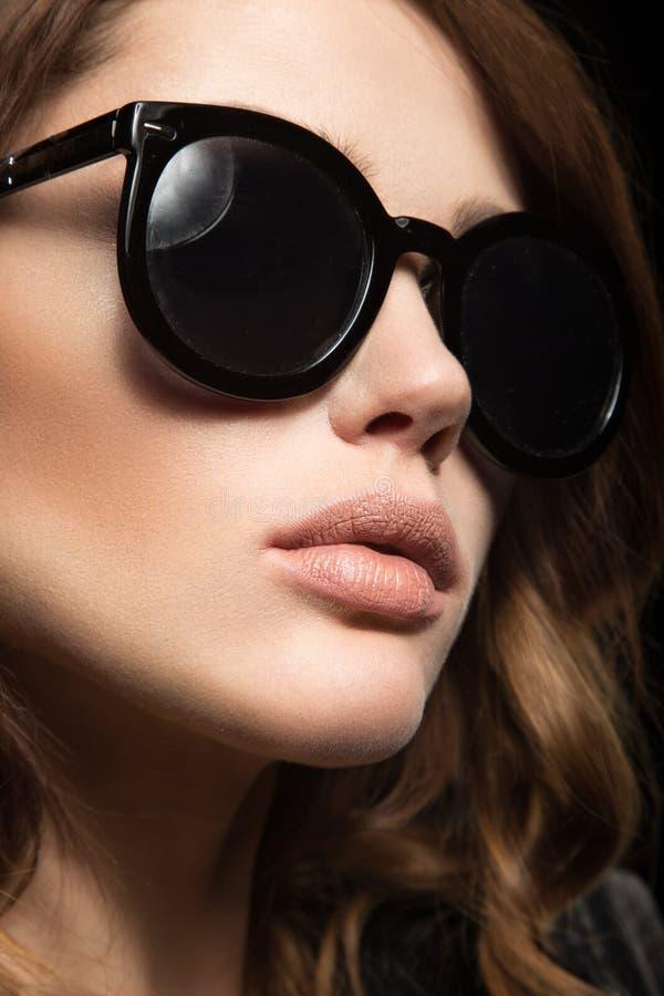 Mooi meisje in donkere zonnebril, met krullen en avondmake-up Het Gezicht van de schoonheid stock foto