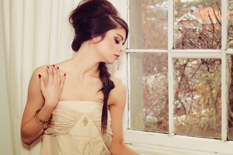 Mooi meisje door venster stock afbeelding