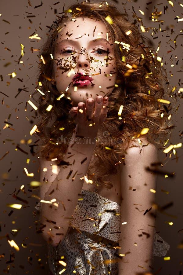 Mooi meisje in een avondjurk en gouden krullen Het model in Nieuwjaar` s beeld met schittert en klatergoud royalty-vrije stock foto