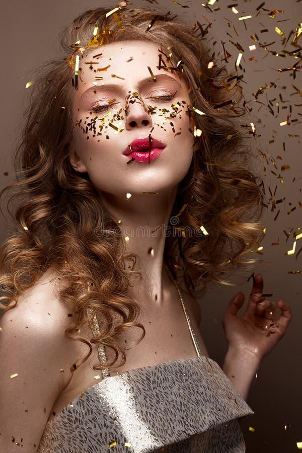 Mooi meisje in een avondjurk en gouden krullen Het model in Nieuwjaar` s beeld met schittert en klatergoud stock afbeeldingen