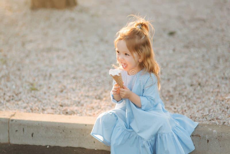 Mooi meisje in een blauwe kleding die een roomijs eten royalty-vrije stock afbeelding