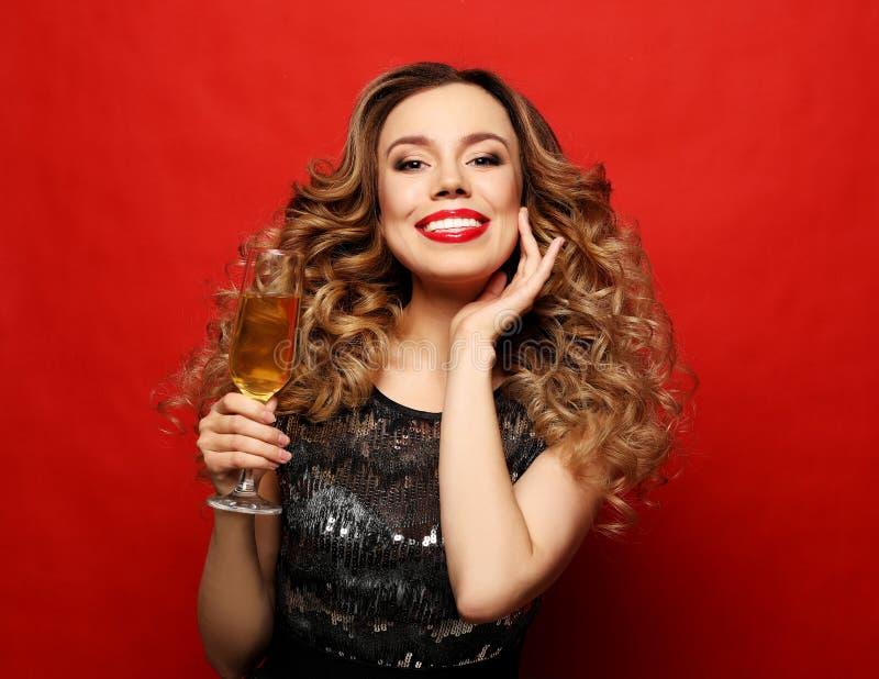 Mooi meisje in een cocktailkleding met avondsamenstelling en krullen die een glas champagne houden royalty-vrije stock foto's