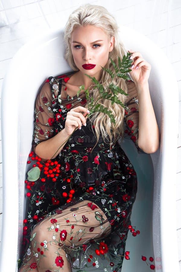 Mooi meisje in een de zomerkleding in de badkamers met bloemen Het Gezicht van de schoonheid royalty-vrije stock fotografie