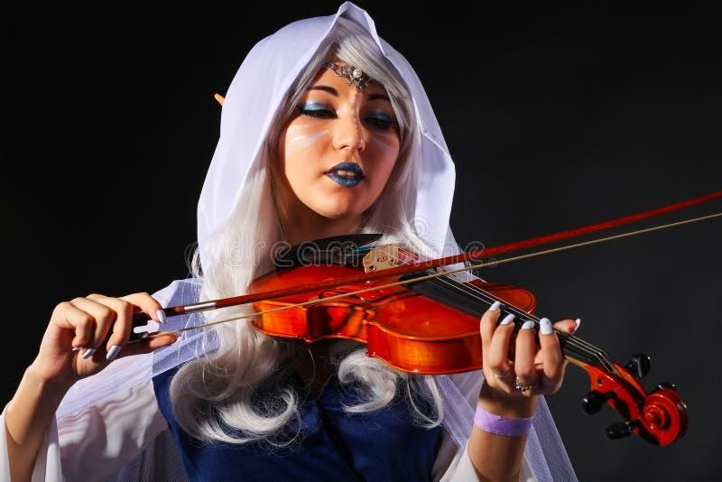 Mooi meisje in een elfkostuum met een viool stock fotografie