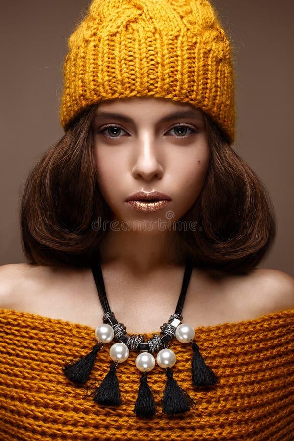 Mooi meisje in een gebreide hoed op haar hoofd en een halsband van parels rond haar hals Het model met zachte samenstelling en go stock afbeelding
