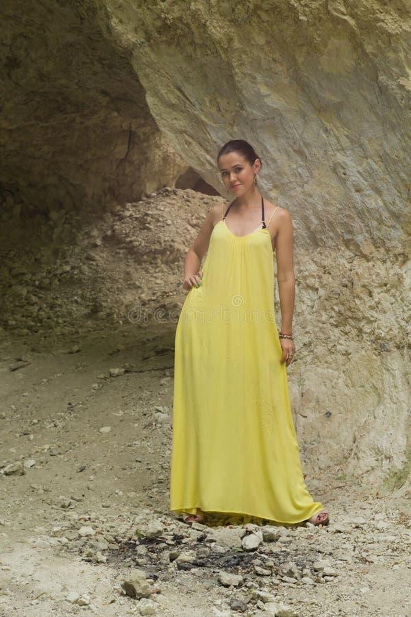 Mooi meisje in een gele kleding dichtbij de rotsen stock afbeeldingen