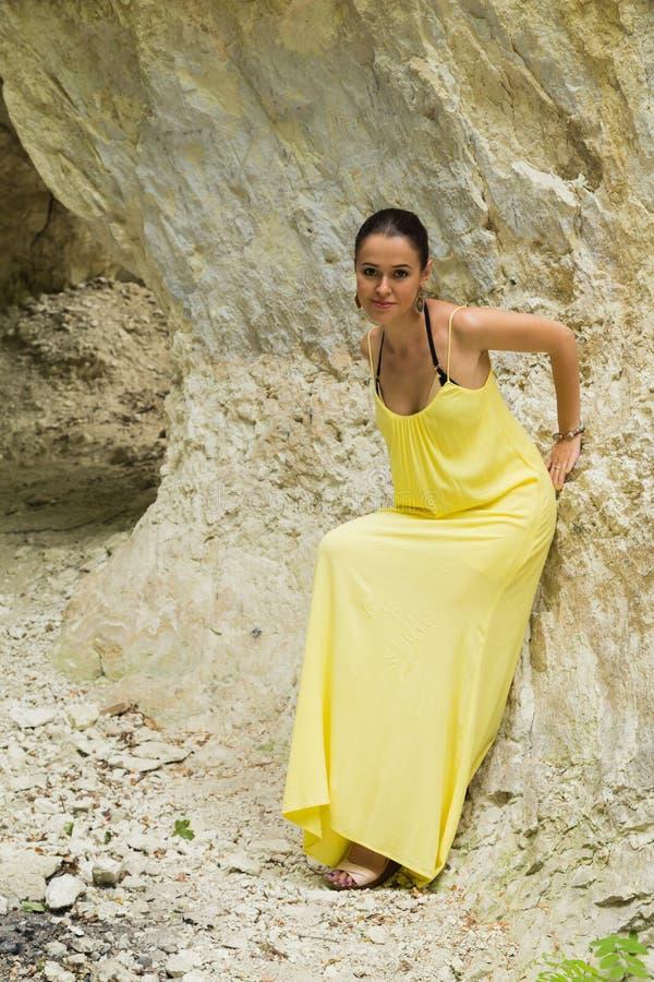Mooi meisje in een gele kleding dichtbij de rotsen royalty-vrije stock foto's