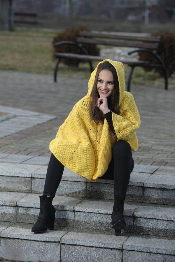 Mooi meisje in een gele met de hand gemaakte gebreide poncho royalty-vrije stock afbeelding