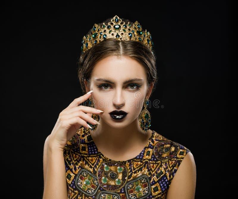 Mooi meisje in een gouden kroon en oorringen op een donkere backgrou royalty-vrije stock afbeelding