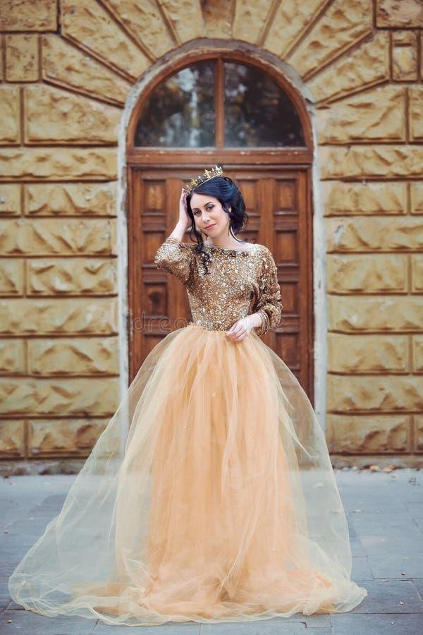 Mooi meisje in een gouden, luxueuze kleding royalty-vrije stock afbeeldingen