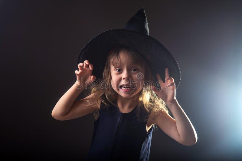 Mooi meisje in een heksenhoed op een donkere achtergrond met vrije ruimte voor uw tekst stock foto's