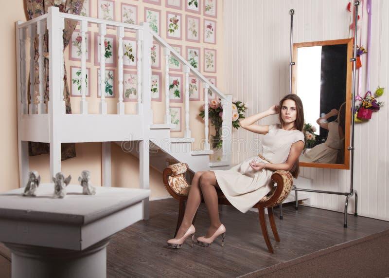 Mooi meisje in een heldere kledingszitting op een stoel stock afbeelding