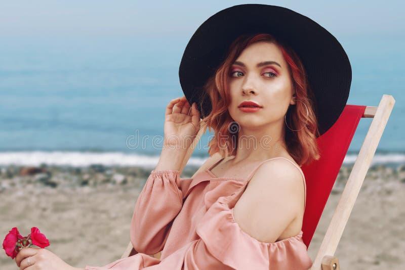Mooi meisje in een hoed met roze haar en mooie make-up die op een lanterfanter tegen het strand en de oceaan liggen stock foto