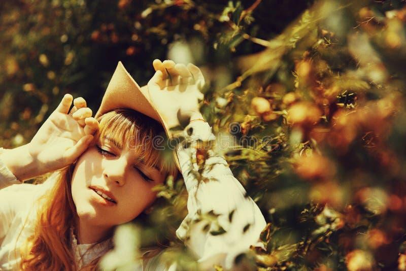 Mooi meisje in een hoed met rozen Zomerpark zonnig stock afbeeldingen