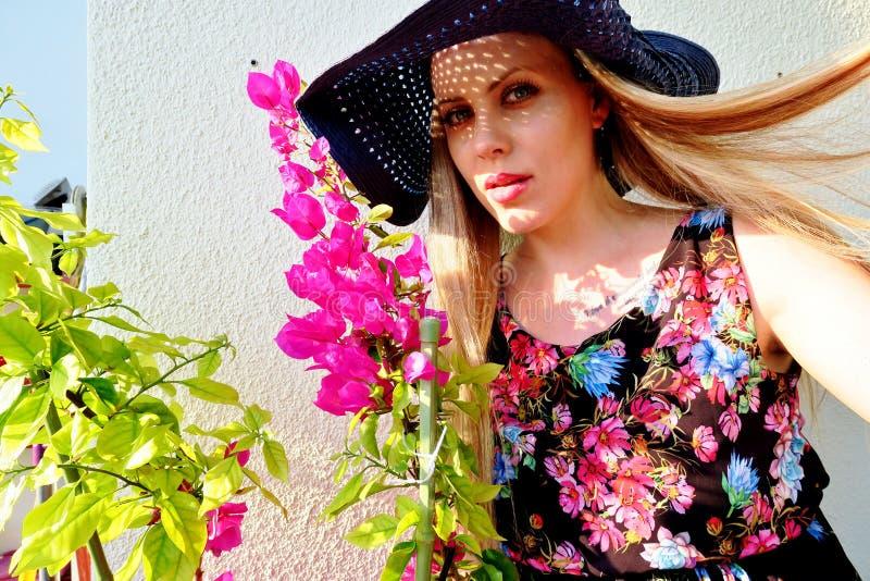 Mooi meisje in een hoed met vliegend haar in de wind stock fotografie