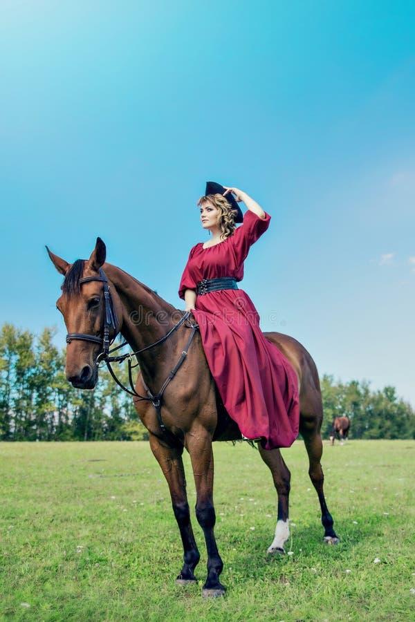 Mooi meisje in een lange rode kleding die een bruin paard berijden tegen een blauwe hemel stock foto's