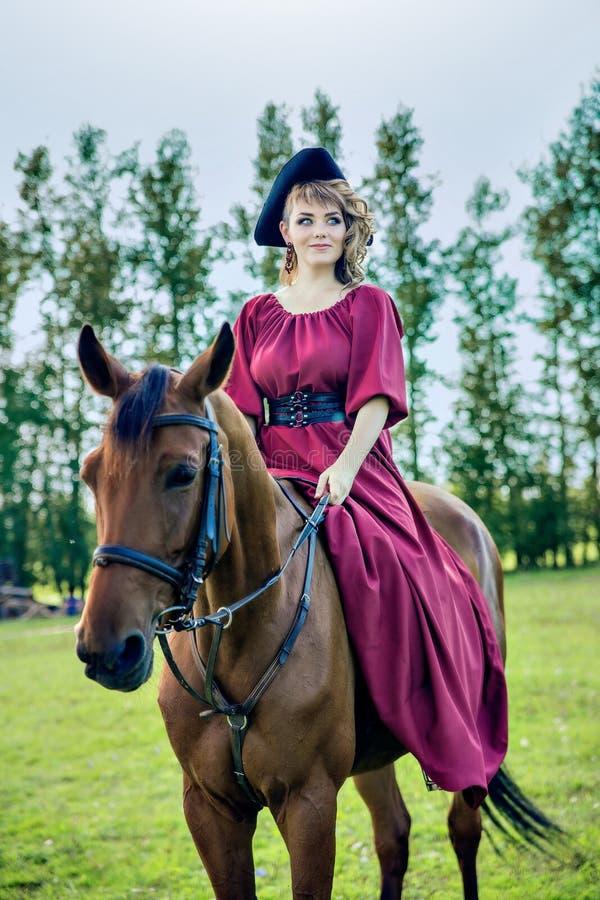 Mooi meisje in een lange rode kleding en in een zwarte hoed met een hoed met opgeslagen randen die een bruin paard berijden stock afbeeldingen