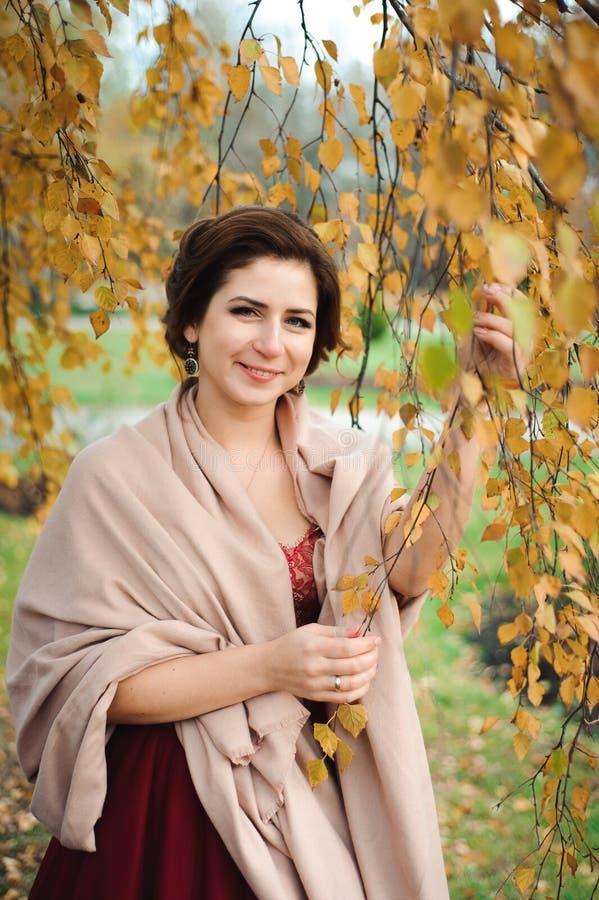 Mooi meisje in een rode kleding in het de herfstbos royalty-vrije stock fotografie