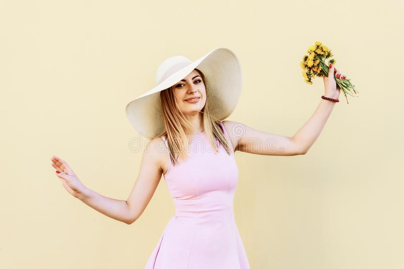 Mooi, mooi, mooi meisje in een roze kleding, in een strohoed die, stellend portret tegen een gele muur glimlachen stock afbeelding