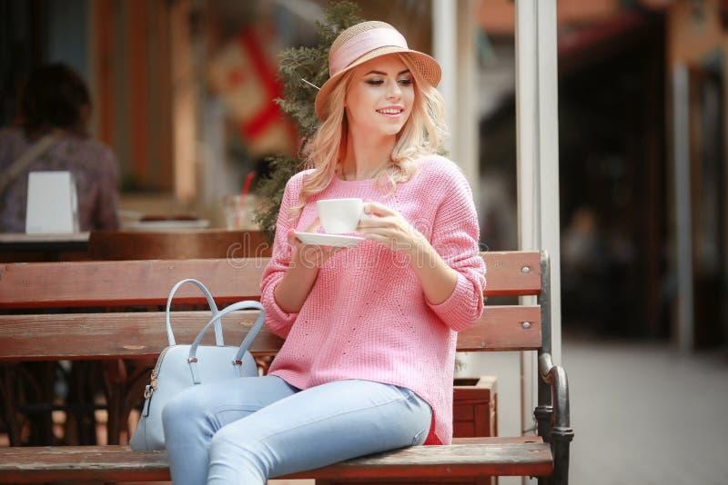 Mooi meisje in een roze kledingszitting in een koffie met een tablet en een Kop van cappuccino Jonge gelukkige vrouw die tablet g stock fotografie