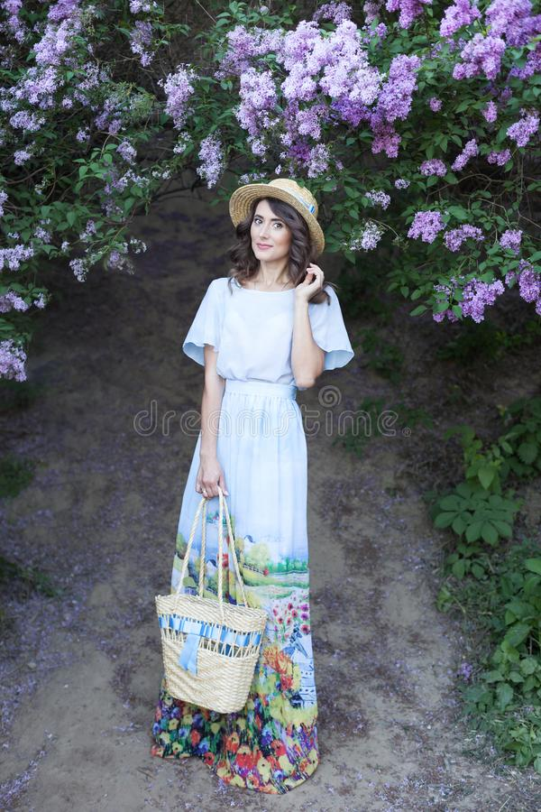 Mooi meisje in een strohoed in een lilac tuin Meisje met lilac bloemen in de lentetijd Het tuinieren Het concept vrouwelijkheid,  royalty-vrije stock fotografie