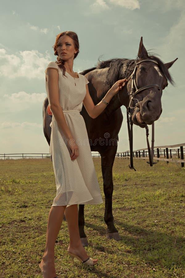 Mooi meisje in een witte toga met paard stock foto