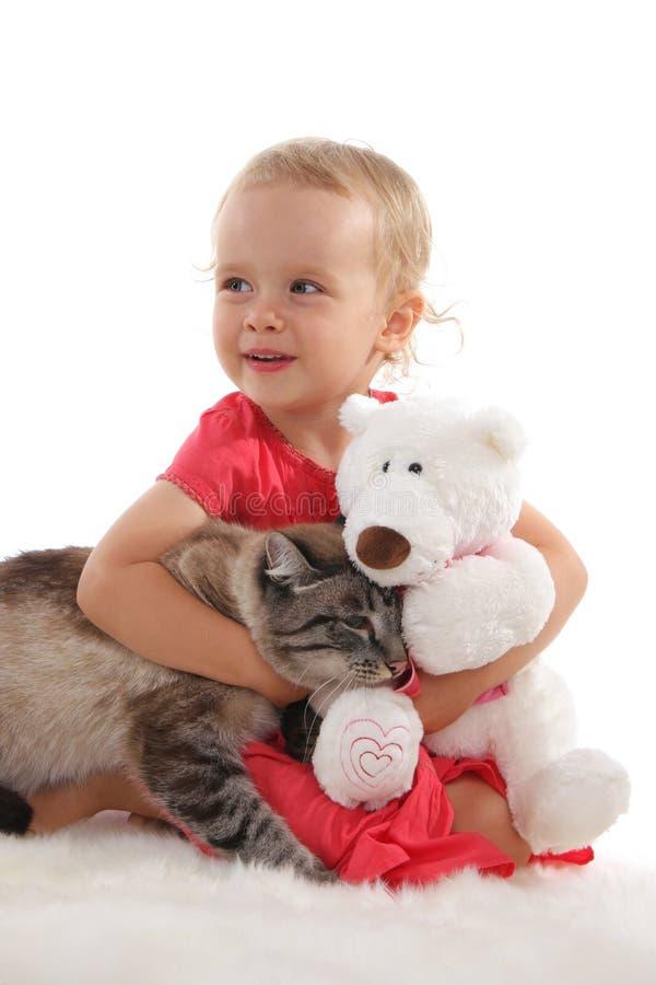 Mooi meisje en een kat en een stuk speelgoed 4 stock foto