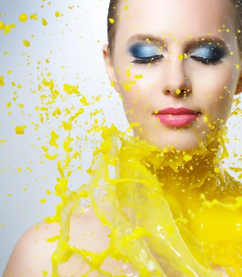 Mooi meisje en gele verfplonsen stock foto's