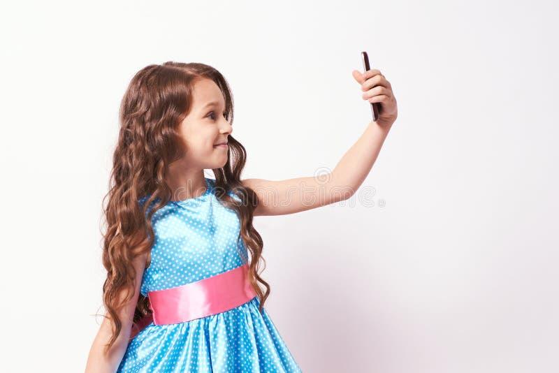 Mooi meisje Foto op telefoon Weelderige blauwe kleding stock foto
