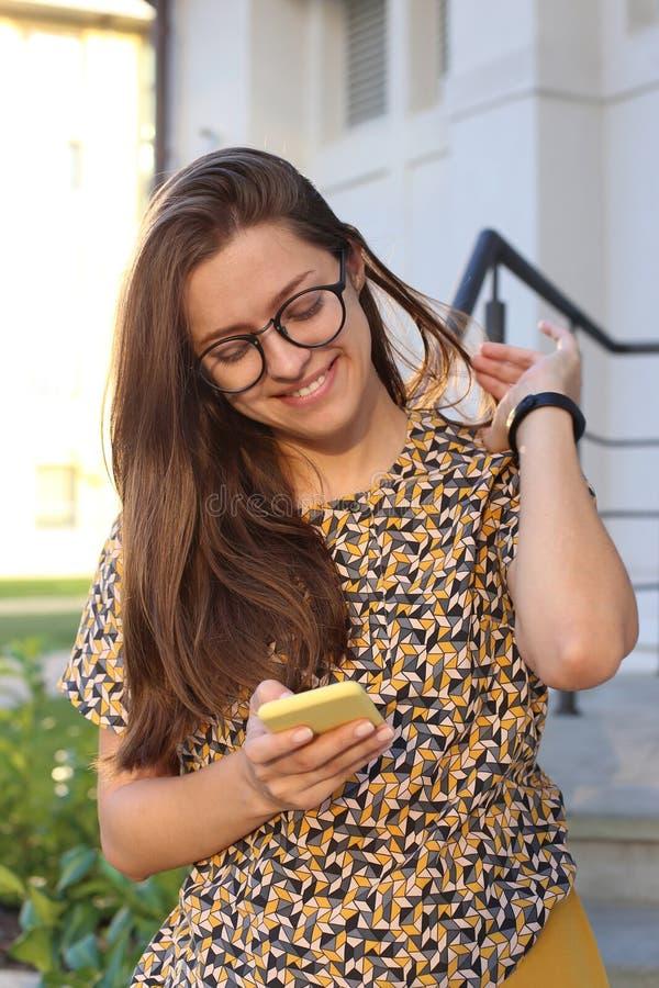 Mooi meisje in glazen die smartphone in openlucht met behulp van royalty-vrije stock afbeelding