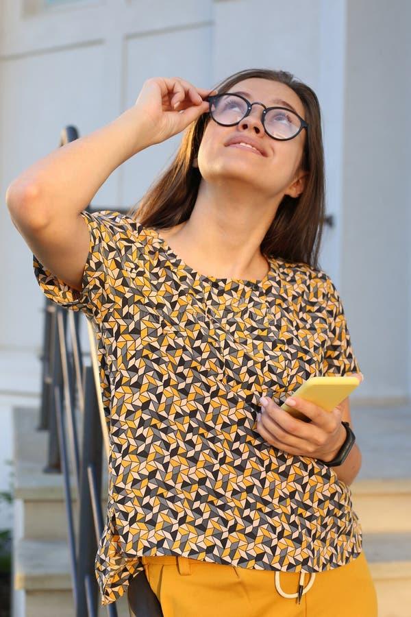Mooi meisje in glazen die smartphone in openlucht met behulp van stock foto's