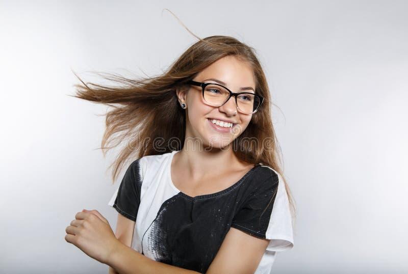 Mooi meisje in glazen met vliegend haar Mooie glimlach Positieve emoties royalty-vrije stock afbeeldingen