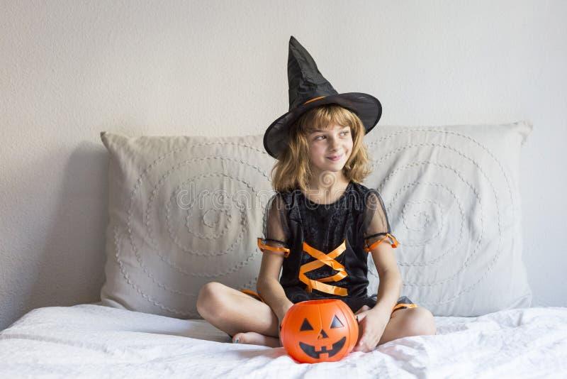mooi meisje glimlachte op bed en droeg een half kostuum. spelen met pompoenen. Thuis, binnenshuis, levensstijl stock foto