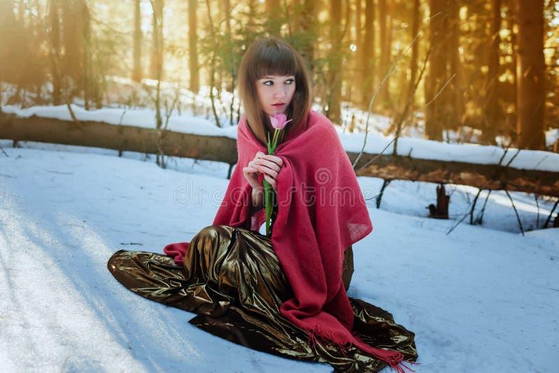 Mooi meisje in Gouden kledingszitting in de sneeuw in de het hout en de aanrakingentulp van de de lentezon royalty-vrije stock afbeelding