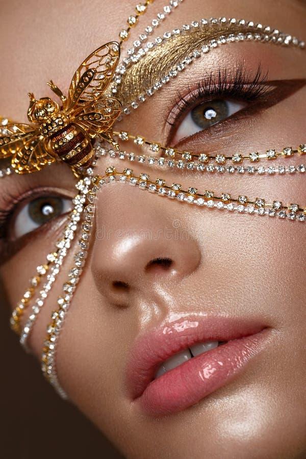 Mooi meisje in gouden masker en heldere avondsamenstelling Het Gezicht van de schoonheid royalty-vrije stock fotografie