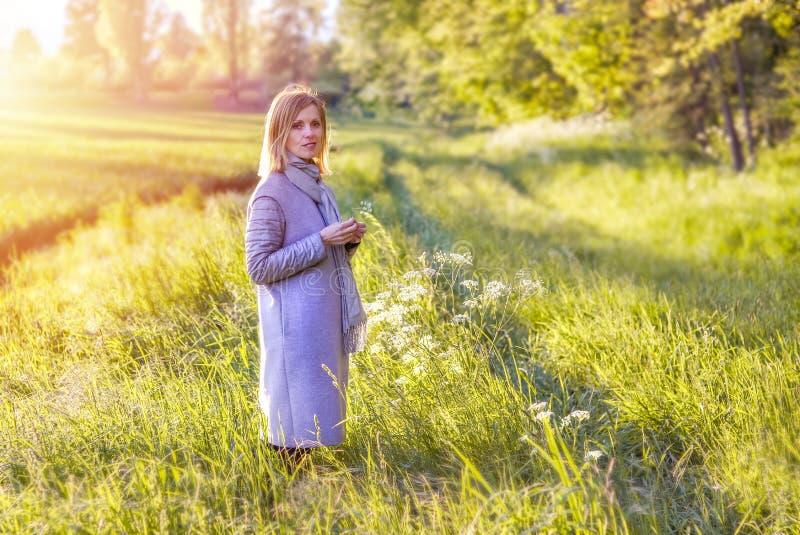 Mooi meisje in grijze laag die op de lentegebied met groen gras en wilde bloemen bij zonsondergang blijven royalty-vrije stock foto's