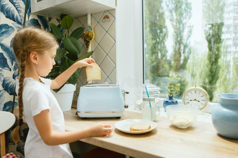 Mooi meisje in haar keuken in de ochtend die ontbijt voorbereiden stock foto